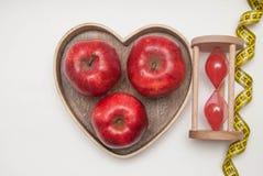 Gesundes Nahrungsmittelkonzept Diät und Eignung Glasuhr und Rot Apple in der Herz-Form-Holzkiste Messendes Band, lokalisiert auf  Lizenzfreies Stockfoto