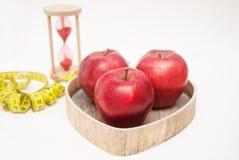 Gesundes Nahrungsmittelkonzept Diät und Eignung Glasuhr und rotes reifes Apple im Herzen formen Holzkiste Cyan-blaues messendes B Lizenzfreie Stockfotografie