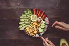Gesundes Nahrungsmittelkonzept Essen des gesunden Salats mit Kichererbse und Gemüse auf dem Holztisch Lebensmittel des strengen V Lizenzfreie Stockfotos