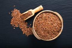 Gesundes Nahrungsmittelkonzept organische Leinsamen im keramischen bolw auf schwarzem Schieferbrett mit Kopienraum lizenzfreies stockbild