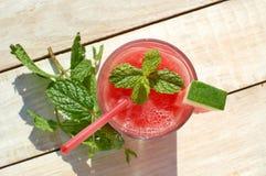 Gesundes neues Smoothiegetränk von der roten Wassermelone, vom Kalk, von der Minze und vom Eisgang Stockfotografie