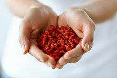 Gesundes organisches Diät-Lebensmittel Frau übergibt voll von Goji-Beeren stockbilder