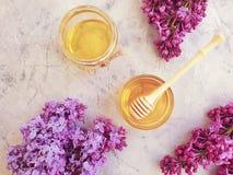 Gesundes Produkt des frischen Bienenhonigs, blühende Flieder auf einem grauen konkreten Hintergrund stockbild