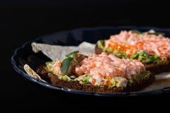 Gesundes Sandwich vom Schwarzbrot, von der reifen Avocado und vom roten Kaviar auf einer blauen Weinleseplatte lizenzfreie stockfotos