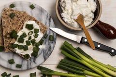Gesundes, vegetarisches Frühstück mit Zwiebel des knusprigen Brotes, des Quarks und des Frühlinges lizenzfreies stockbild