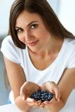 Gesundes Vitaminlebensmittel Schöne lächelnde Frau mit Blaubeeren Stockfotos