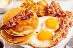 Gesundes volles amerikanisches Frühstück mit Ei-Speck Pfannkuchen und Latkes stockfotos
