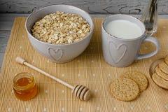 Gesundes Vollkornfrühstück: Hafermehl, Milch, Kekse, Honig und Vase mit Rosen Lizenzfreie Stockfotos
