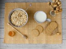 Gesundes Vollkornfrühstück: Hafermehl, Milch, Kekse, Honig und Vase mit Rosen Stockfotos