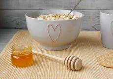 Gesundes Vollkornfrühstück: Hafermehl, Milch, Kekse, Honig und Vase mit Rosen Lizenzfreies Stockfoto
