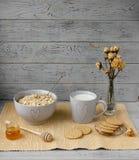 Gesundes Vollkornfrühstück: Hafermehl, Milch, Kekse, Honig und Vase mit Rosen Stockbild