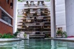 Gesundes Wasser des Badekurortes und künstliches Wasserfallgebäude im Erholungsort Lizenzfreie Stockfotografie