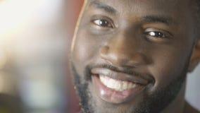 Gesundes weißes Lächeln des aufgeregten Afroamerikanermannes, der Kamera, Nahaufnahme untersucht stock video