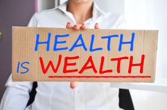 Gesundheit ist das Reichtumssagen geschrieben auf ein Pappzeichen, das von einer Frau gehalten wird Stockbild
