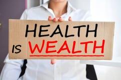 Gesundheit ist das Reichtumssagen geschrieben auf ein Pappzeichen, das von einer Frau gehalten wird Lizenzfreies Stockfoto