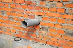Gesundheitliches Abwasserrohr in der Haus-Grundmauer Lizenzfreies Stockbild