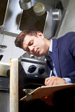 Gesundheits-Inspektor, der Oven In Commercial Kitchen betrachtet Lizenzfreie Stockfotografie