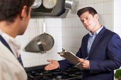 Gesundheits-Inspektor-Sitzung mit Chef In Restaurant Kitchen stockbilder