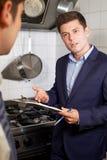 Gesundheits-Inspektor-Sitzung mit Chef In Restaurant Kitchen Stockbild
