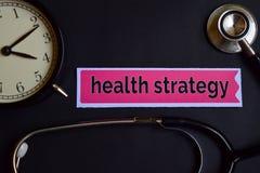 Gesundheits-Strategie auf dem Druckpapier mit Gesundheitswesen-Konzept-Inspiration Wecker, schwarzes Stethoskop lizenzfreie stockfotografie
