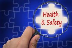 Gesundheits- und Sicherheitswort Vergrößerungsglas und Puzzlespiele Lizenzfreie Stockbilder