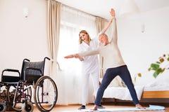 Gesundheitsbesucher und älterer Mann während des Hausbesuchs stockfotografie