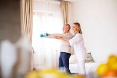 Gesundheitsbesucher und älterer Mann während des Hausbesuchs stockfotos