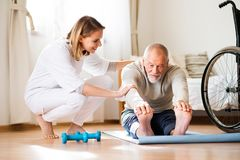 Gesundheitsbesucher und älterer Mann während des Hausbesuchs stockbilder