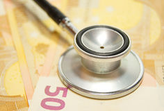Gesundheitspflegekosten - Stethoskop auf Geld backgroun Lizenzfreies Stockfoto