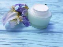 Gesundheitssalben-Irisblume der Sahnefeuchtigkeitscreme kosmetische aromatische organische auf einem blauen hölzernen Hintergrund Lizenzfreie Stockfotos