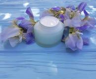 Gesundheitssalben-Irisblume der Sahnefeuchtigkeitscreme kosmetische auf einem blauen hölzernen Hintergrund Lizenzfreies Stockbild
