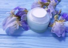 Gesundheitssalben-Irisblume der Sahnefeuchtigkeitscreme kosmetische organische auf einem blauen hölzernen Hintergrund Lizenzfreie Stockfotos