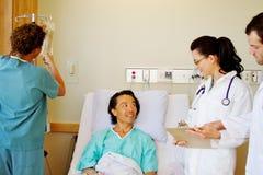 Gesundheitsteam, das Patientensorgfalt bespricht Lizenzfreie Stockfotos