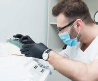 Gesundheitswesen-, Beruf-, Stomatologie- und Medizinkonzept - lächelnder männlicher junger Zahnarzt über Hintergrund des Ärztlich Lizenzfreie Stockfotografie