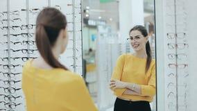 Gesundheitswesen, Sehvermögen und Visionskonzept Glückliche Frau, die Gläser am Optikspeicher vor Spiegel wählt stock video footage