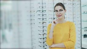 Gesundheitswesen, Sehvermögen und Visionskonzept Hübsche Frau, die in den Brillen am Optikspeicher aufwirft Hintergrund von Shopr stock video footage