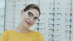 Gesundheitswesen, Sehvermögen und Visionskonzept Hübsche Frau, die in den Brillen am Optikspeicher aufwirft Hintergrund von Shopr stock footage