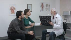 Gesundheitswesen und medizinisches Konzept Doktor mit den Patienten, die Röntgenstrahl betrachten stock footage