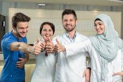 Gesundheitswesen- und Medizinkonzept - attraktiver männlicher Doktor vor medizinischer Gruppe im Krankenhaus, das sich Daumen zei stockfotografie