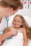 Gesundheitswesenfachmann, der oben auf kleinem Mädchen überprüft Stockfoto