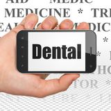 Gesundheitswesenkonzept: Hand, die Smartphone mit zahnmedizinischem auf Anzeige hält lizenzfreie stockbilder