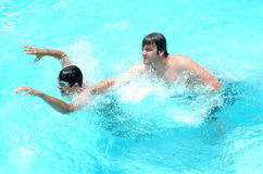 Get Away. Teenage boys playing in the pool. One tries to escape as the other one grabs to bully stock photos