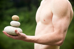 Get the balance. Strong athletic hand holding a pile of stones in balance. Get the balance concept Royalty Free Stock Images