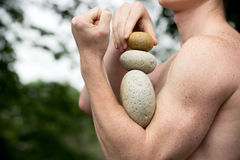 Get the balance. Strong athletic hands holding a pile of stones in balance. Get the balance concept Stock Image