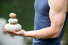 Get the balance. Strong athletic hand holding a pile of stones in balance. Get the balance concept Stock Photos