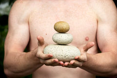 Get the balance. Strong athletic hands holding a pile of stones in balance. Get the balance concept Royalty Free Stock Image