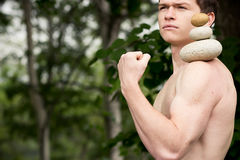 Get the balance. Strong athletic man holding a pile of stones in balance. Get the balance concept Stock Images