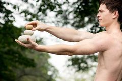 Get the balance. Strong athletic man holding a pile of stones in balance. Get the balance concept Royalty Free Stock Photo