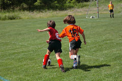 Get That Ball 6. Girl chasing soccer ball down the field Royalty Free Stock Image