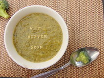 Get better soon written in vegetable soup with spoon. And vegetable next to it royalty free stock images